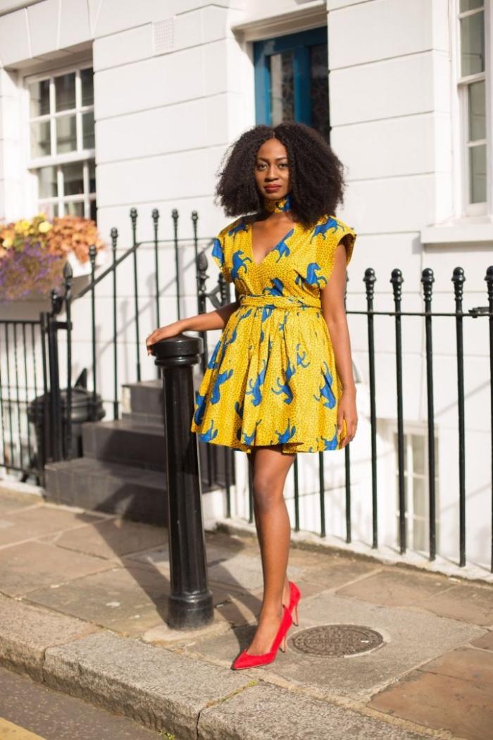 une jolie robe en wax patineuse à motif cheval bleu sur fond jaune fluo et à taille cintrée associée à une paire d'escarpins rouge vermillon