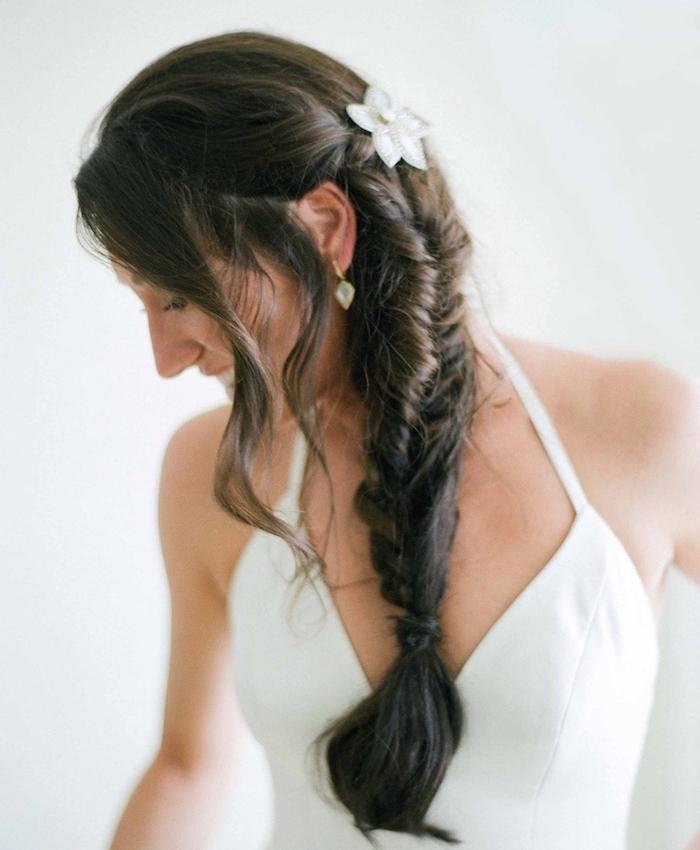 tresse mariée sur cheveux chatain foncé, mèches libres et une décoration de fleurs blanche, robe de mariée simple
