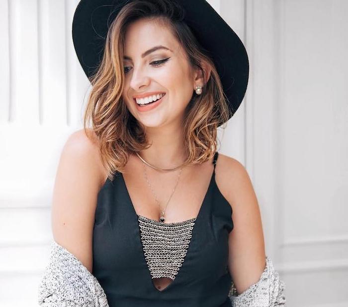 robe d été glamour noire, chapeau noir sur cheveux en carré long ondulé avec une mèche sur le côté, maquillage simple