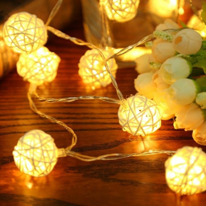 des boules illuminantes, une guirlande lumineuse led, roses blanches, table de chevet dans une chambre d'adulte, guirlande lumineuse interieur