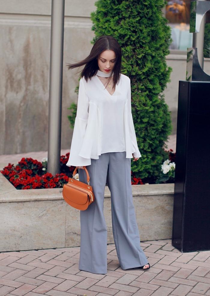 modèle de pantalon fluide femme habillé en gris clair avec blouse loose en blanc, modèle de sac à main de cuir marron