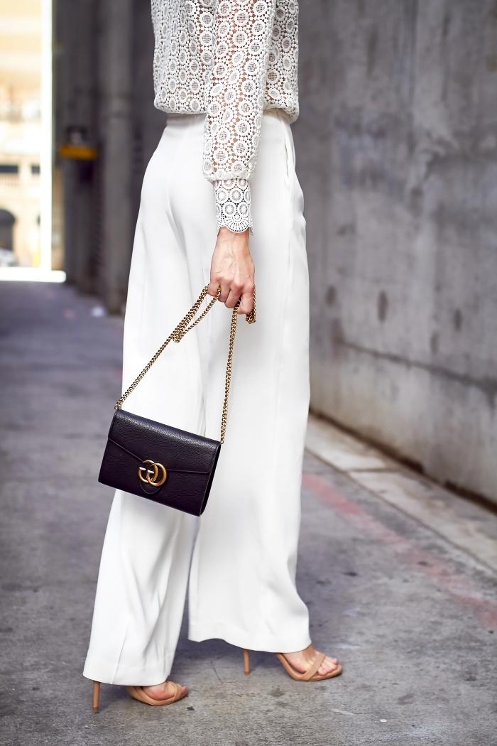 vision totale blanche en pantalon fluide femme et blouse broderie aux motifs géométriques avec sandales beige et sac à main noir