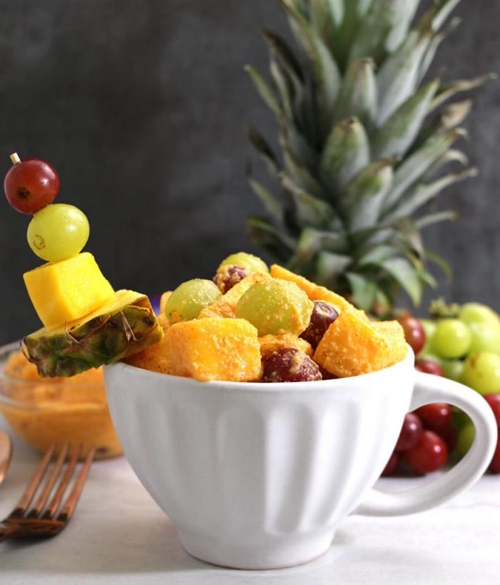 une salade ete tropicale aux épices, servie avec une brochette de fruits