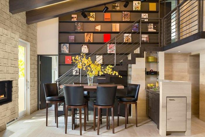 chaises en couleur wengé, table rectangulaire, escalier avec rambarde, mur wengé aux cadres photos