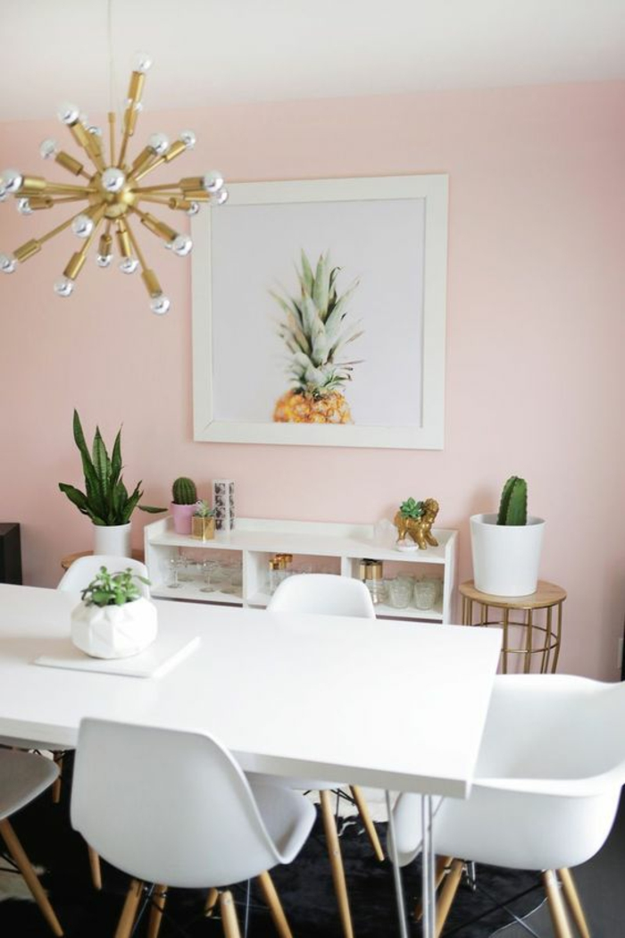deco rose poudré, murs en couleur rose pale, peinture rose poudré, luminaire en métal doré avec des boules en verre blanc mat, fauteuils en plastique blanche, table rectangulaire blanche, tableau avec un ananas au cadre blanc