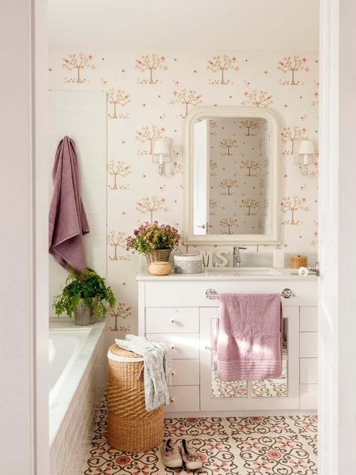 les carreaux de ciment et le papier peint champêtre derrière le lavabo apportent une ambiance douce et romantique dans cette petite salle de bains