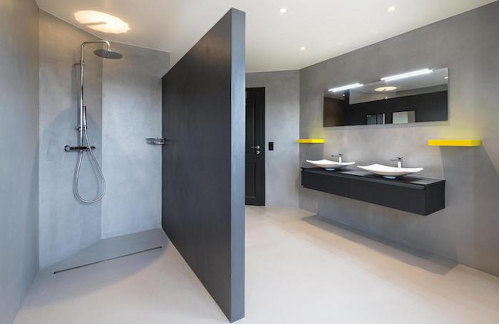 mur de sdb en béton ciré gris clair avec paroi separation de salle de bain sur sol cimenté