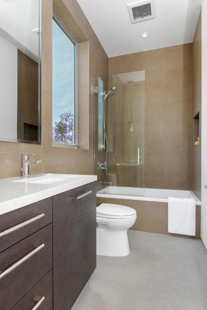 modèle petite salle de bain avec baignoire aux murs beige et plancher gris avec plafond blanc, meuble lavabo à comptoir blanc et portes foncées