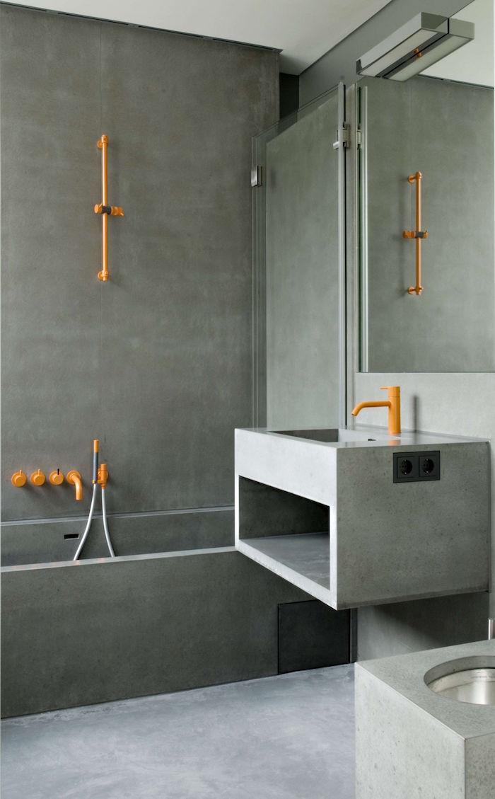 douche à l'italienne beton ciré sur mur salle de bain moderne et design avec lavabo en ciment et plomberie metal orange