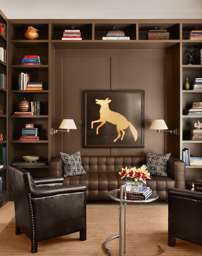 salon wengé, mur avec étagères et panneau mural foncé, sofa cuir marron, petite table ronde