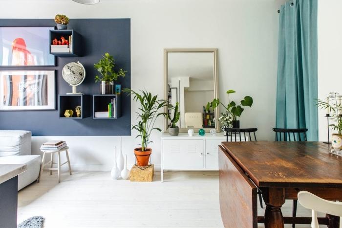 deco salon bleu et blanc aux accents verts pour une ambiance qui appelle au calme et à la détente, coin de mur peint en bleu marine pour dynamiser l'intérieur blanc