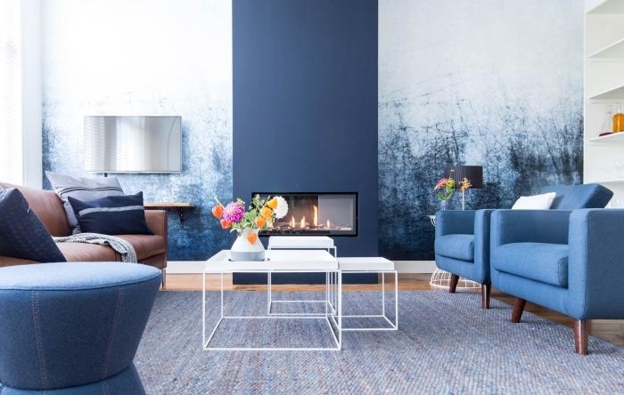 deco salon bleu et blanc associant harmonieusement les couleurs froides, la cheminée peinte en bleu marine assortie au papier peint imprimé graphique du mur attenant