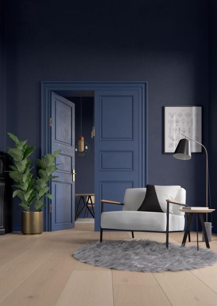 le bleu marine mat des murs et de la porte révèle sa luminosité grâce à quelques accents noir et laiton, fond bleu foncé pour une sensation de profondeur