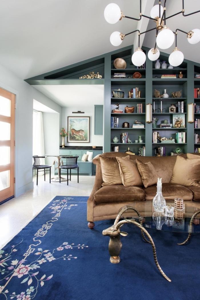 idée pour une deco bleu canard dans le salon, un mur bibliothèque couleur bleu canard aux petites touches de laiton qui s'harmonise avec le canapé en velours marron