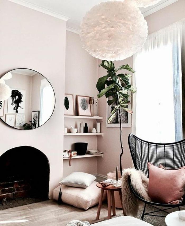 quelle couleur associer au gris, fauteuil en métal noir, luminaire en forme de pompon, grand miroir rond au cadre noir, salon avec cheminée, murs rose pale, un mur avec trois étagères blanches, chambre rose poudré et taupe