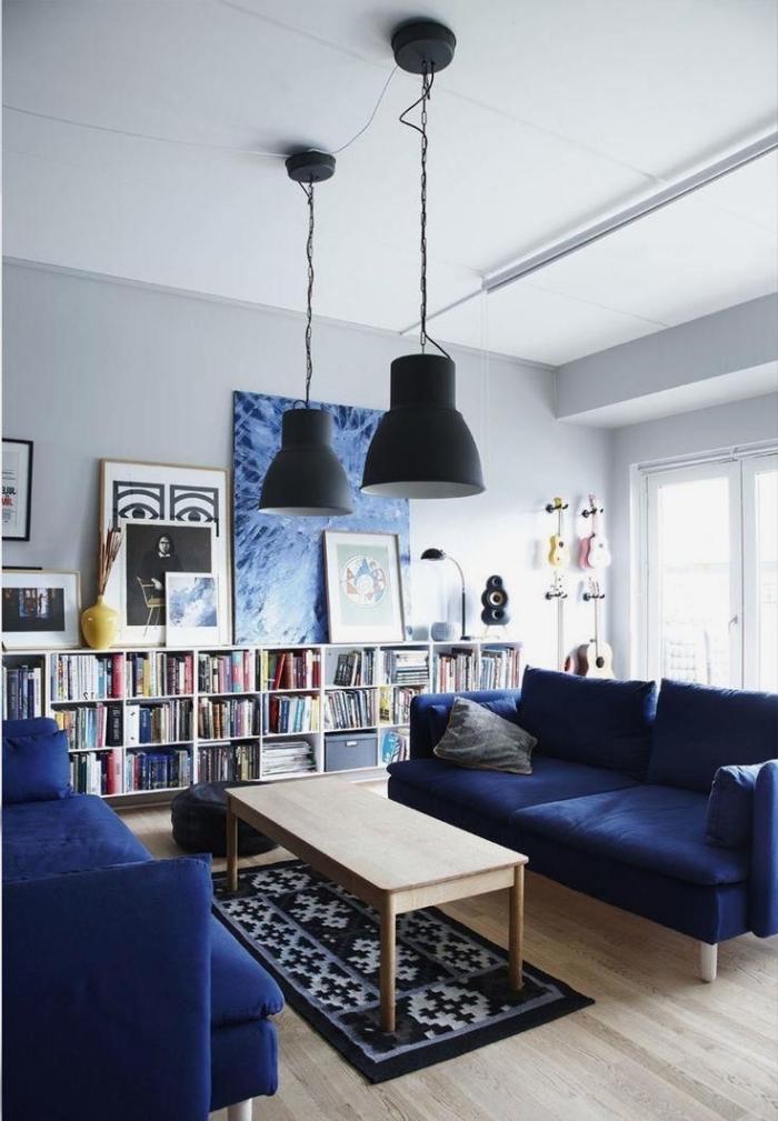 la galerie murale reprend les couleurs du canapé bleu marine et des luminaires industriels pour une déco salon harmonieuse et appaisante