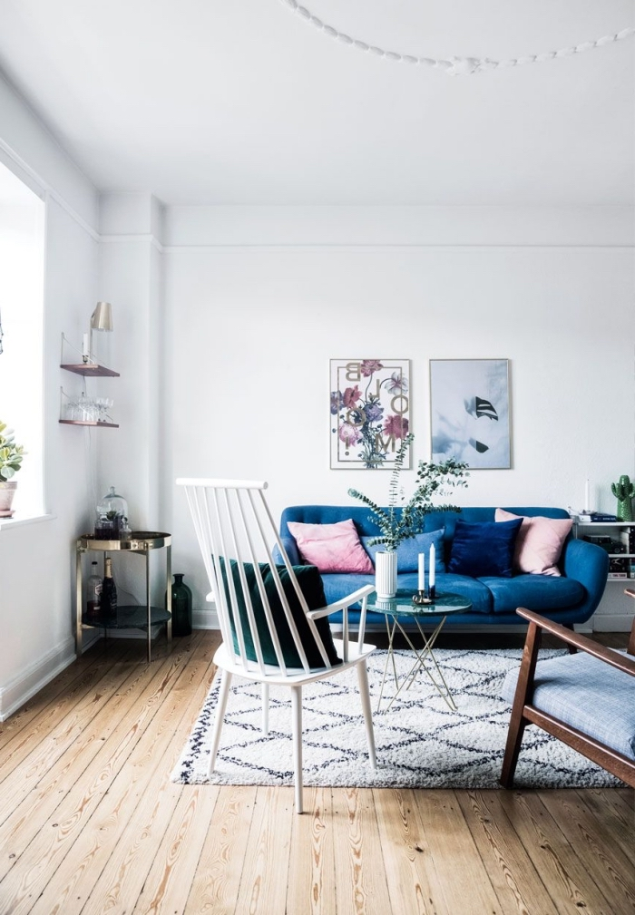 salon blanc scandinave avec un canapé bleu roi sublimé par des coussins rose et bleu indigo