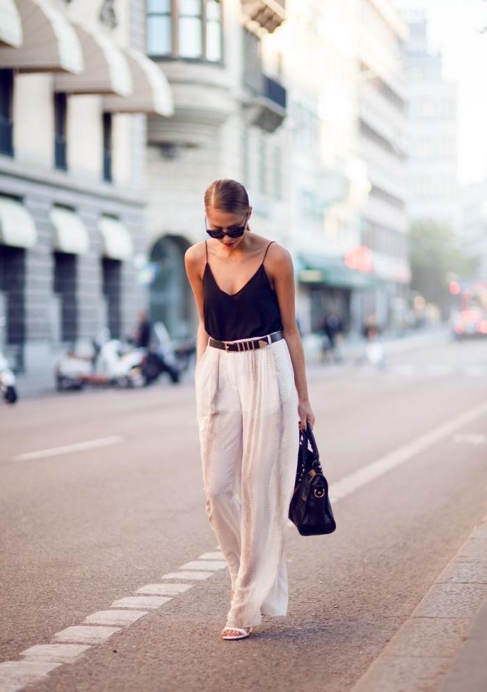 tenue casual smart en pantalon large blanc avec ceinture noire et top à décolleté et bretelles noris, coiffure cheveux en queue de cheval bas