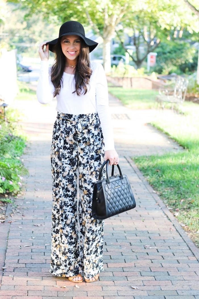 vision chic femme en pantalon taille haute à design fleuri avec blouse blanche et accessoires noirs sac à main et capeline