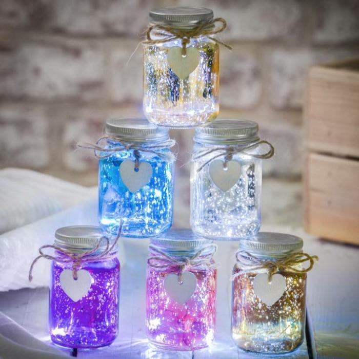 guirlande lumineuse interieur, pots en verre avec des couvercles en métal, guirlandes aux couleurs acidulées, sept pots posés les uns au-dessus des autres