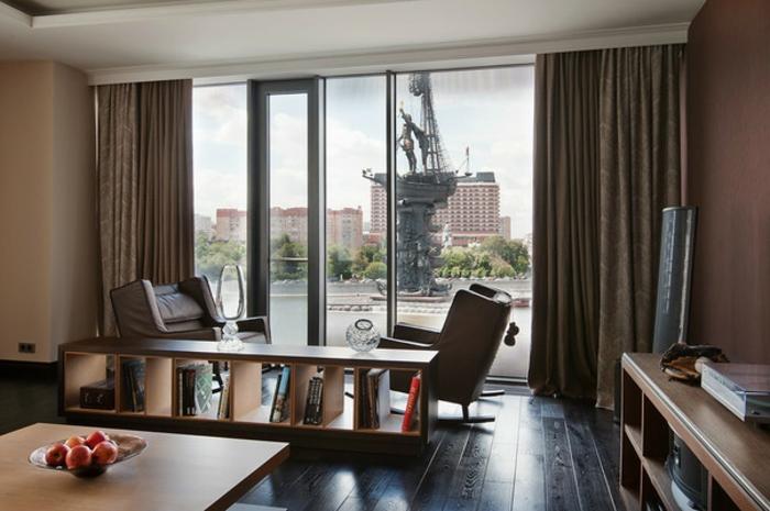 intérieur marron, table en bois carrée, fauteuils sombres, étagère autoportante, grande fenêtre