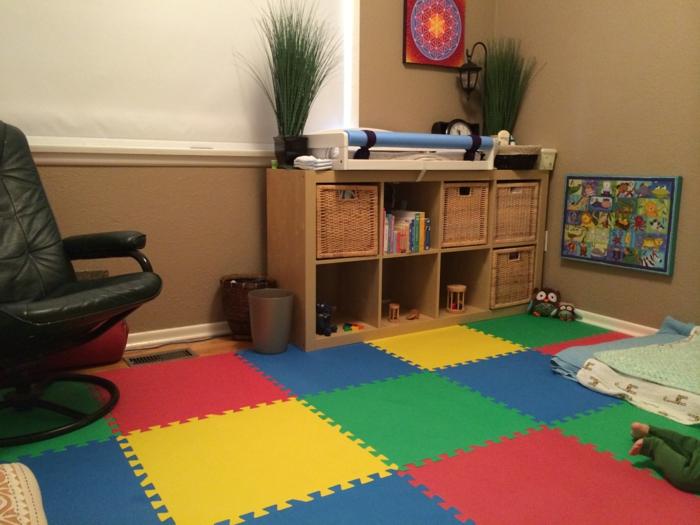 murs en marron clair, meuble de rangement avec des casiers, lit bébé sans barreau, fauteuil simili cuir noir, sol recouvert de tapis coloré en vert, jaune, rouge et bleu