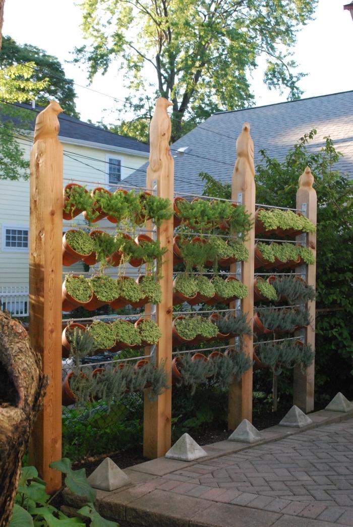 un mur végétal extérieur facile à entretenir, composé de pots suspendus sur un support de cadre en bois et grillage, aménagement petit jardin de ville