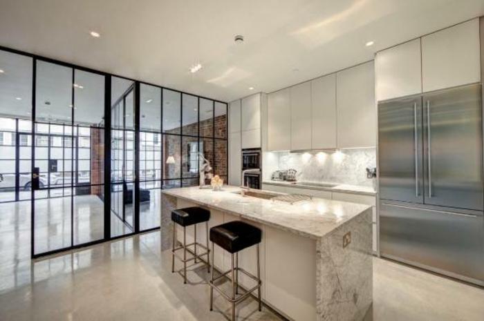 intérieur spacieux style loft, deux tabourets noirs près d'un ilot de cuisine blanc, grande verriere d'atelier