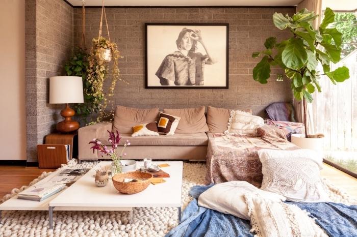 déco de salon bohème chic aux murs en briques grises avec parquet de bois, modèle de canapé d'angle couvert de coussins berbères