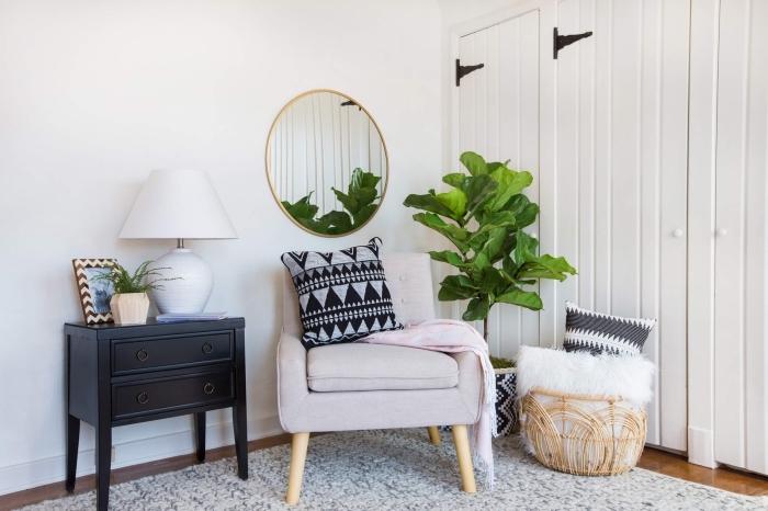 deco boheme chic dans une pièce blanche avec parquet en bois foncé et armoire noire décoré de lampe blanche et vase en bois clair