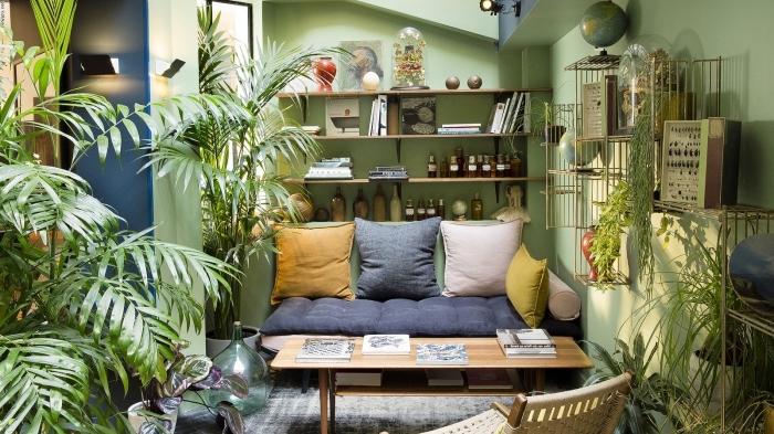 idée pour une deco ethnique dans un petit salon aux murs verts avec plantes vertes, modèle de canapé bas couvert de coussins