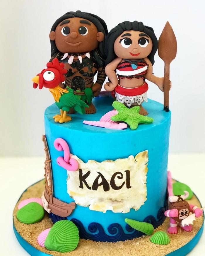 modèle de deco vaiana sur un gâteau DIY au glaçage bleu turquoise avec figurines des personnages Vaiana et Maui