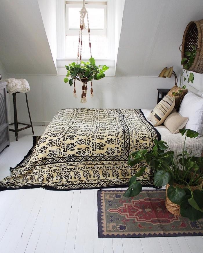 idée comment aménager une pièce aux combles de style bohème chic, chambre à coucher avec grand lit et plantes vertes
