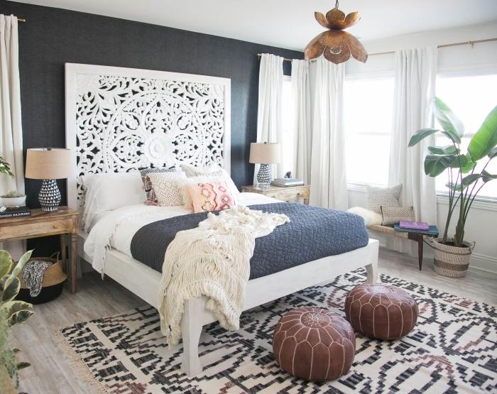decoration boheme dans une pièce aux murs blancs et gris anthracite, modèle de pouf en cuir marron et tapis aux motifs ethniques blanc et noir