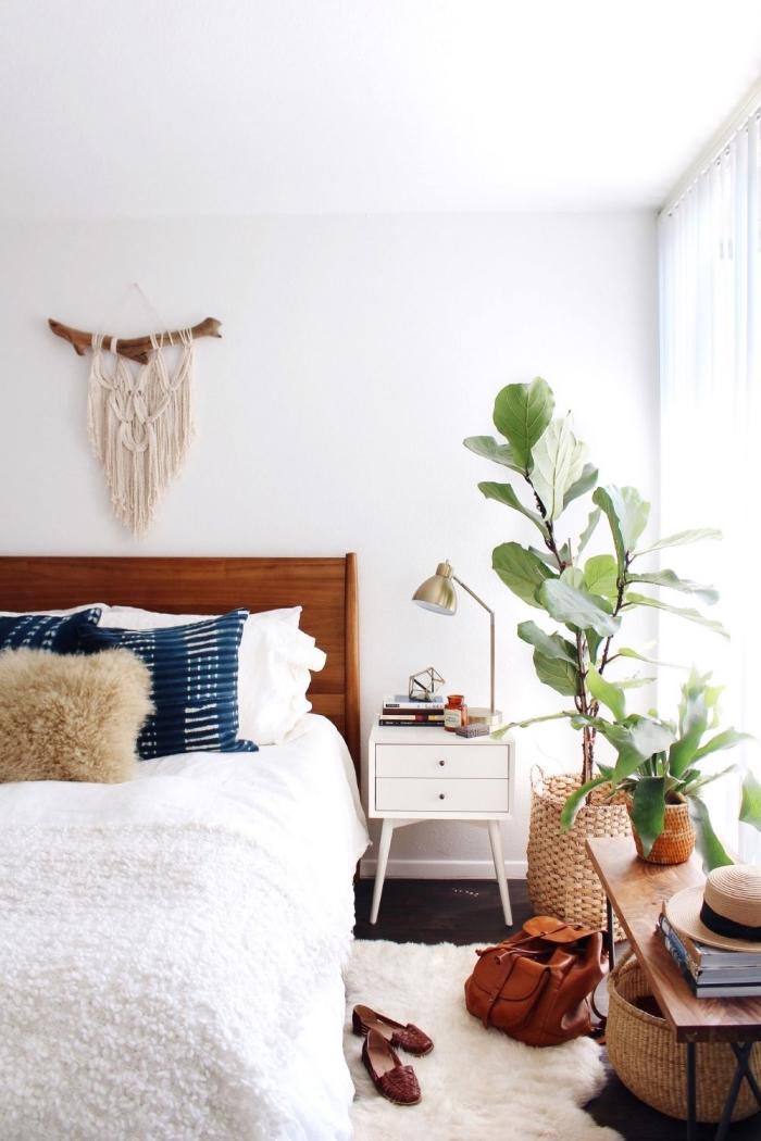 exemple de déco cocooning dans une chambre à coucher bohème aux murs blancs avec paniers en paille et meubles de bois