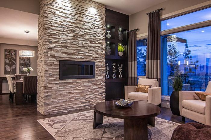 cheminée parement pierre, table basse ovale, tapis original, fauteuils beiges, grande fenêtre