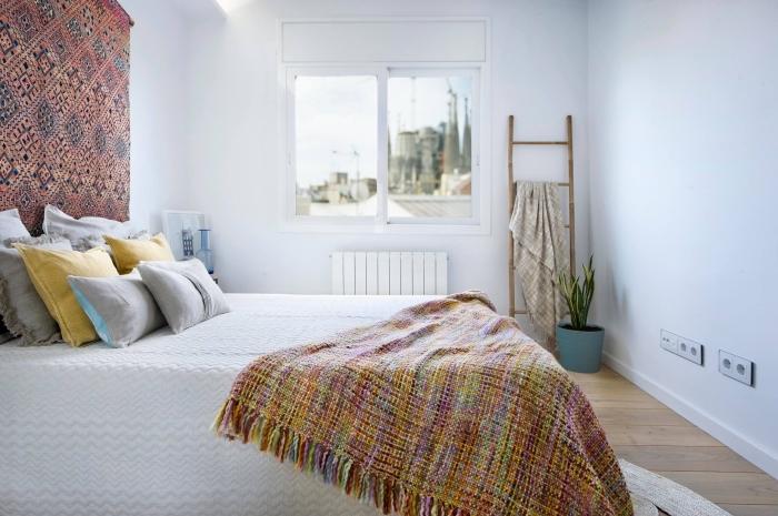 pièce à deco boheme chic aux murs blancs et parquet blanc avec tapisserie murale aux motifs ethniques et plaid multicolore à franges