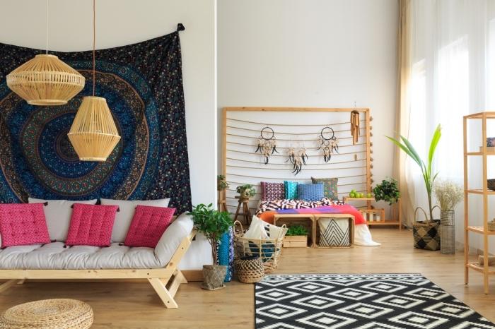 déco logement étudiant à design chic et boheme, salon aménagé avec meubles de bois avec canapé couvert de coussins roses et tapisserie murale foncée