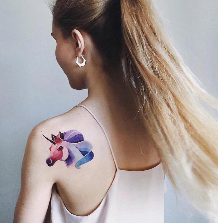 photo de tatouage de licorne en couleurs aquarelle rose bleu violet sur épaule de femme