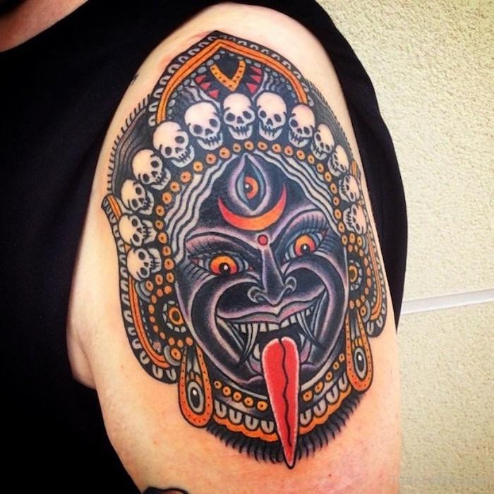 tatouage masque dieu deesse asie thailand en couleurs sur epaule et bras homme