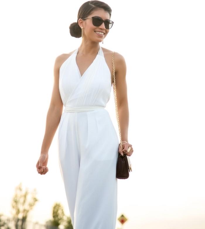 femme élégante en combinaison blanche avec ceinture combinée avec sac à main et paire de lunettes en noir