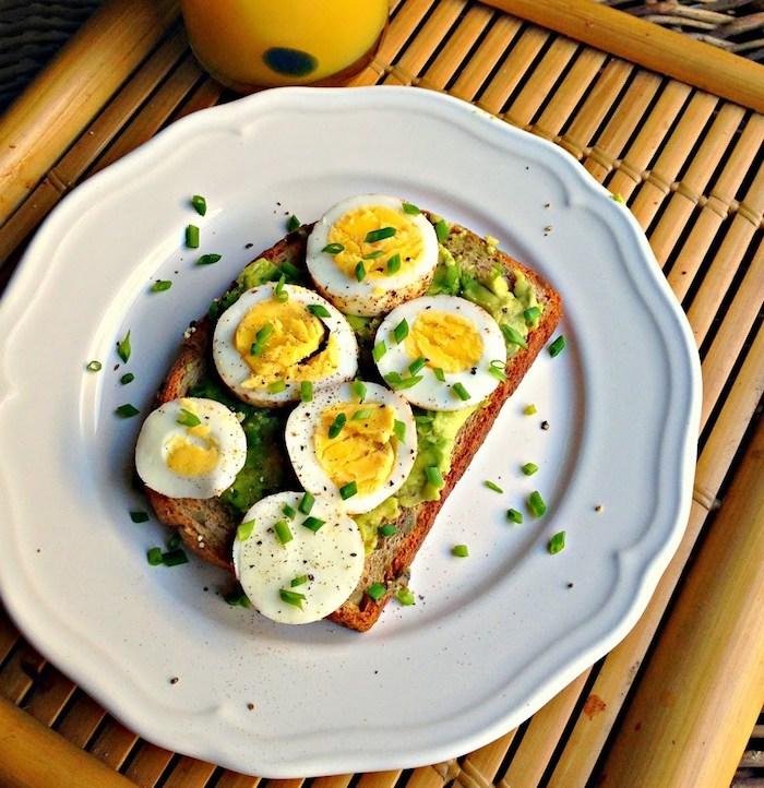 toast tartiné d avocat avec des rondelles d oeufs en top, déjeuner du matin à faire soi meme