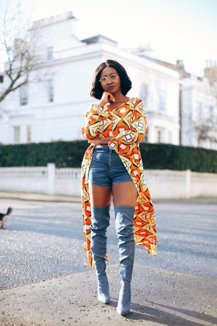 top asymétrique en pagne africain à motifs jaune et orange combiné avec un short en jean et des cuissardes jean pour une allure urbaine chic originale