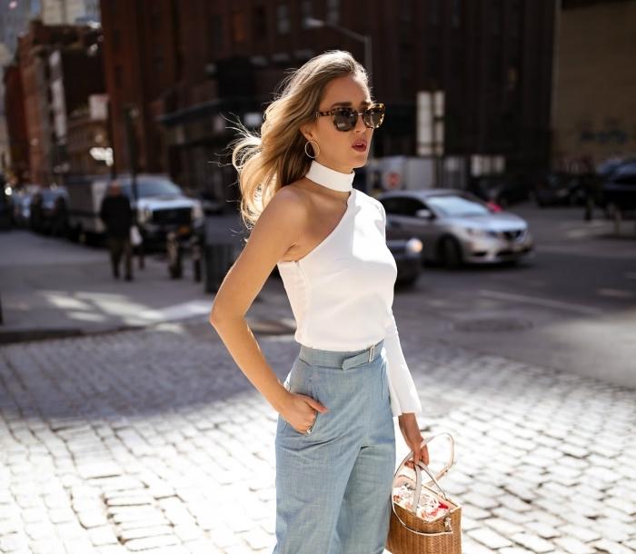 look chic femme en pantalon large bleu clair avec top blanc à col asymétrique et sac à main en jute, maquillage avec lèvres marron