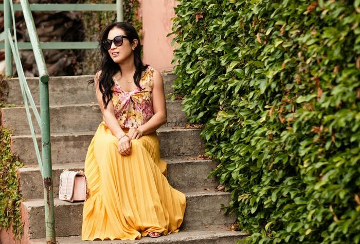 joli top floral en couleurs claires, jupe longue plissée, lunettes de soleil