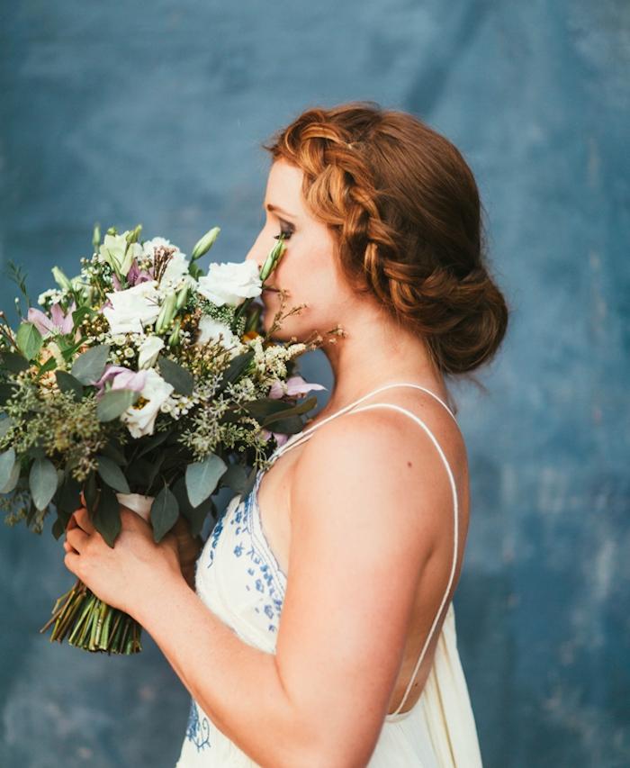 coiffure chignon tresse avec une tresse de côté sur cheveux longs roux, robe de mariée blanches à motifs bleus