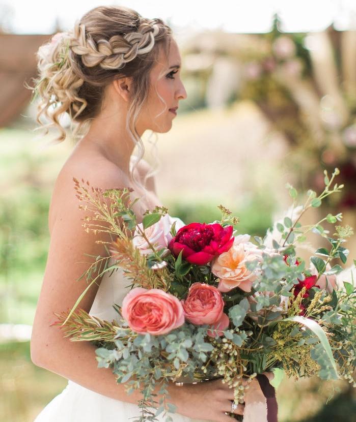 tresse sur le coté qui va en arrière de la tete, cheveux attachés ondués blond foncé avec des mèches blonds claires balayage, bouquet de mariee champetre