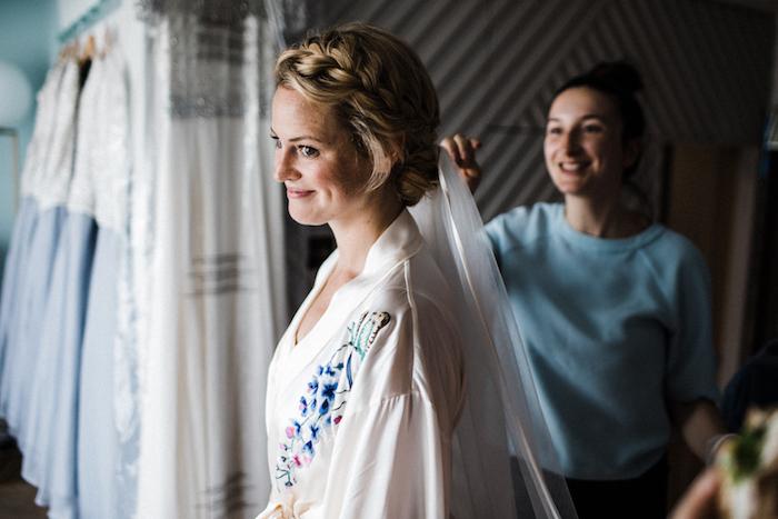 tresse en couronne autour de la tete, coiffure classique de mariée, voile blanche, maquillage mariée naturel