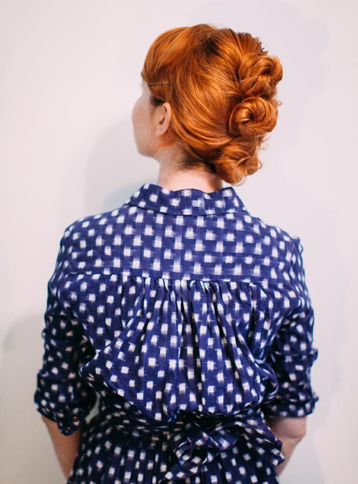 chignon trile sur cheveux acajou, chemise bleue à motif blancs, tenue casuelle chic