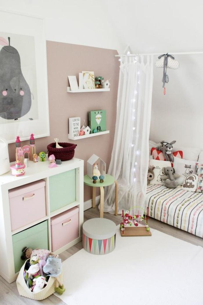 cabane enfant lit en bois blanc, chambre montessori, mur en taupe murs en blanc, tableau avec une poire grise souriante, rideaux voilages avec une guirlande de boules de coton blanches